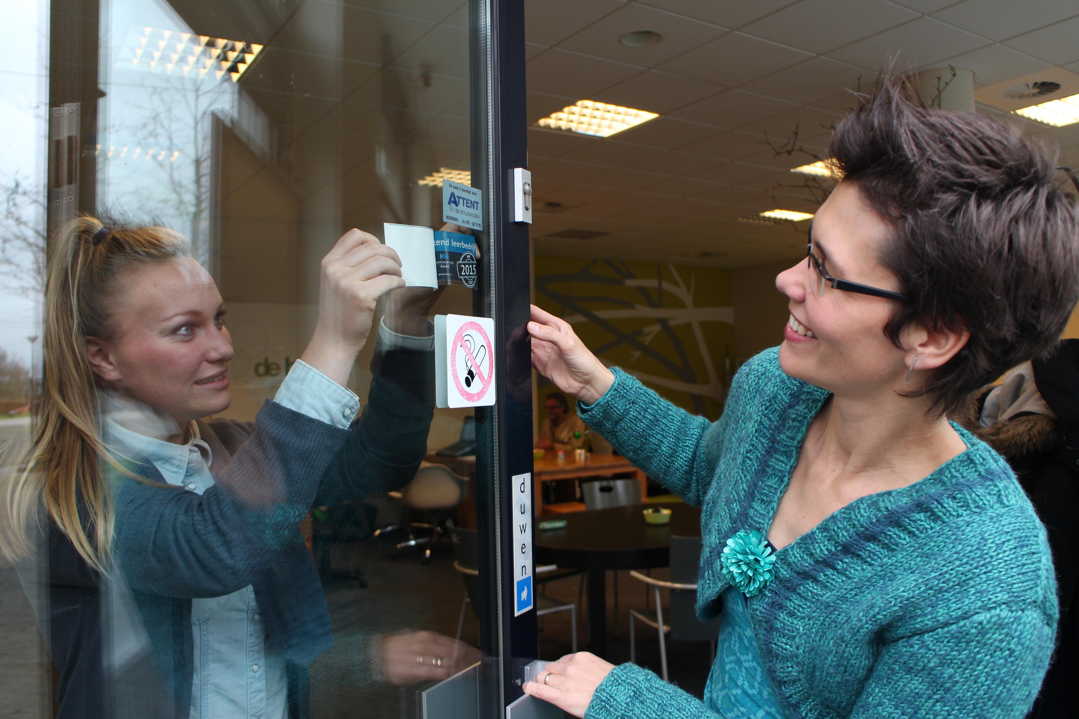 Stagiaire Julia Samsom plakt onder toeziend oog van interieurarchitect en eigenaar Daphne van der Knijff-Looman van VDKL interieurarchitectuur de erkenningssticker op de deur van het bedrijfspand.